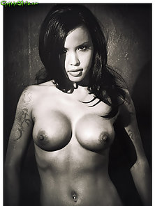 Tattooed Eurasian beauty on fur in black and white